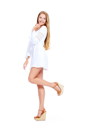 Attractive young woman in a white summer dress and sandals. Isolated over white. Stockfoto