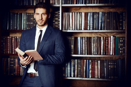 Respectable young man in the old library. Classic vintage interior. Archivio Fotografico