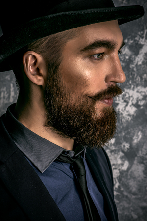 Gentleman z broda i wąsy na sobie elegancki garnitur i cylinder. Stary styl mody.