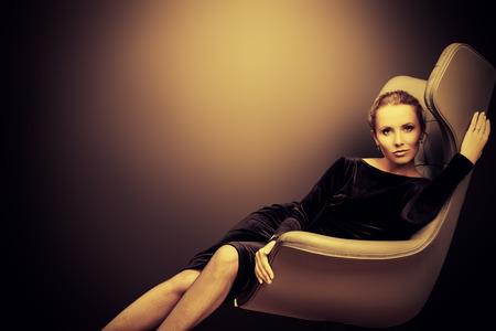 Portret van een prachtige modieuze model zittend in een stoel in Art Nouveau stijl. Business, elegante zakenvrouw. Interieur, meubels.