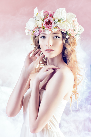 Sensual blonde girl with flowers in her hair. Fashion model. Spring look.