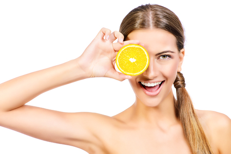 Joyful young woman holding juicy oranges before her eyes. Healthy eating concept. Diet. Isolated over white.
