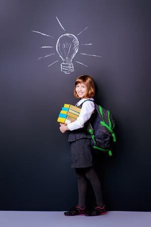 Educatief concept. Glimlachend schoolmeisje dat zich met boeken en schooltas bevindt door een bord. Ruimte kopiëren.