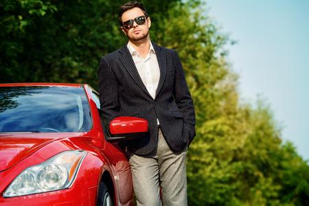 彼の新しいスポーツカーでハンサムな若い男。