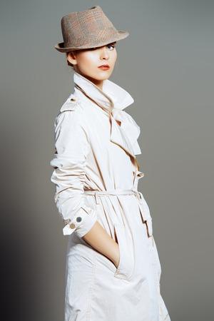 Retrato de un modelo elegante de la manera que presenta en el estudio en un abrigo y sombrero. Belleza, moda. El estilo de negocios.