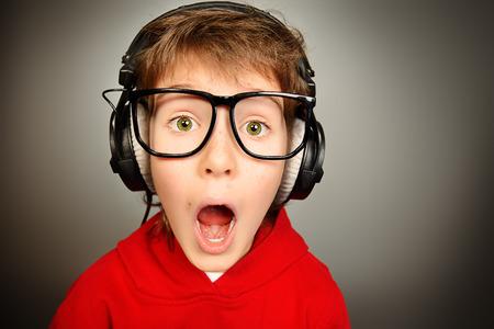 gamer garçon drôle dans un casque et des lunettes regardant la caméra et en criant. Studio shot.