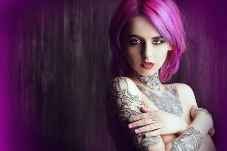 スタイリッシュな深紅の髪と暗いグランジ背景にポーズをとって彼女の体に入れ墨を持つ美しい若い女性。髪の色。化粧品、メイクアップ。タトゥ
