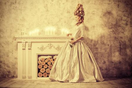 ルネサンスのスタイルで髪を緑豊かな中世のドレスでエレガントな若い女性。セピア色。