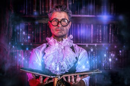 Crazy medieval scientist working in his laboratory with old manuscripts.