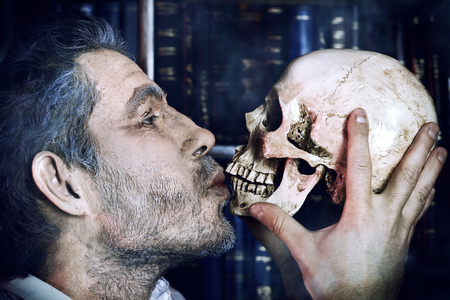 Close-up portrait of an old medieval scientist holding a skull.