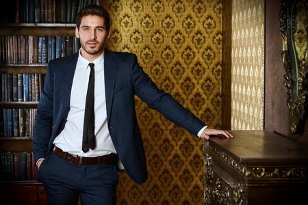Respectabele jonge man die zich door een open haard in een kamer met een klassieke inter.