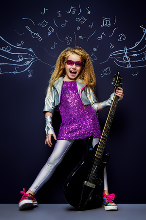 Little rock star singing with her electric guitar over musical background. Music concept. Banco de Imagens