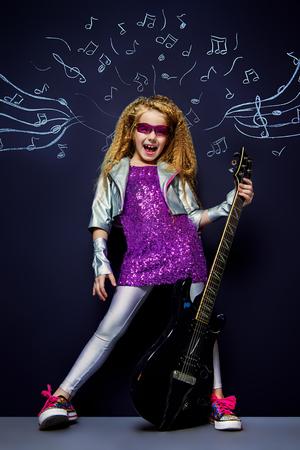 Little rockster zingen met haar elektrische gitaar over muzikale achtergrond. Muziek concept.