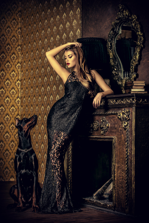 Beautiful lady with her dog in a room with luxurious classic interior. Fashion. Reklamní fotografie