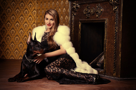 彼女の犬と暖炉のそばで座っている貴重な宝石や毛皮コートを着た美しい女性。クラシックなインテリア。美容、ファッション。 写真素材