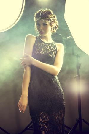 Impresionante modelo de belleza que presenta en el estudio en destellos de luz. Modelo de manera profesional. Celebridad.