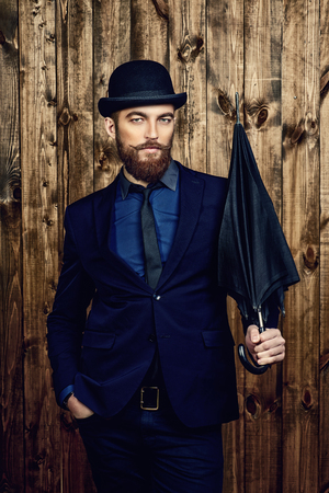 Elegant man with beard and mustache wearing suit and bowler hat. Old style fashion. Stok Fotoğraf