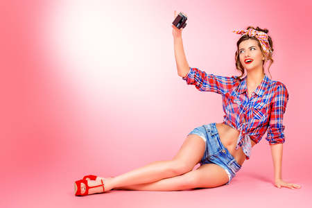 Full length portrait of a beautiful young woman with pin-up make-up and hairstyle posing over pink background with camera. 版權商用圖片