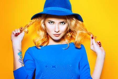 concept de mode Bright. Belle fille avec des cheveux blonds bouclés porter robe bleue posant sur fond jaune.