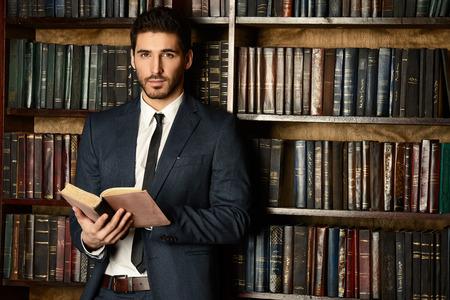 Porządny młody człowiek w starej bibliotece. Classic vintage inter.