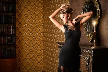 Elegante jonge vrouw in zwarte avond jurk poseren in vintage interieur. Mode-shot.
