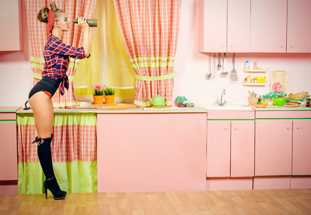 Lovely pin-up girl stands on a pink kitchen and through binoculars. Retro style. Fashion.