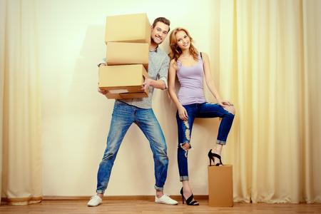 Happy jeunes personnes qui se déplacent dans une nouvelle maison. Réparation de l'appartement. Immobilier, hypothèque.