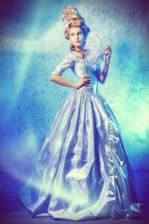 Full length portrait of a beautiful young lady in a luxurious historical dress and high hairdo. Baroque and Renaissance style. Elegant Ice Queen over frozen background.