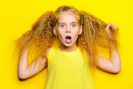 노란색 배경 위에 아름다운 금발 머리와 함께 즐거운 어린 소녀. 아이 스타일. 헤어 스타일.