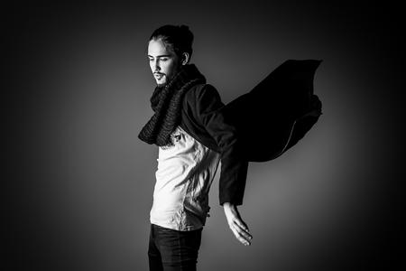 Fashion shot van een knappe mannelijke model in zwart pak poseren in beweging over grijze achtergrond. Men's schoonheid. Stockfoto - 54385476