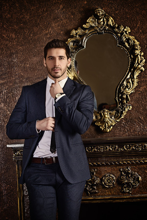 Respectable young man standing by a fireplace in a room with classic interior. Luxury. Mens beauty, fashion.