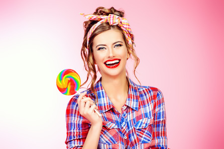 Sexy pin-up girl in jeans shorts and a shirt alluring with bright lollipop over pink background. Beauty, fashion.