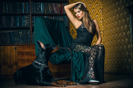 Bella signora con il suo cane in una stanza con lussuoso interno classico. Moda.
