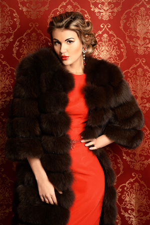Portrait of a beautiful woman in red dress and luxurious fur coat alluring by vintage wallpaper. Luxury, rich lifestyle. Jewellery. Fashion shot. Stockfoto