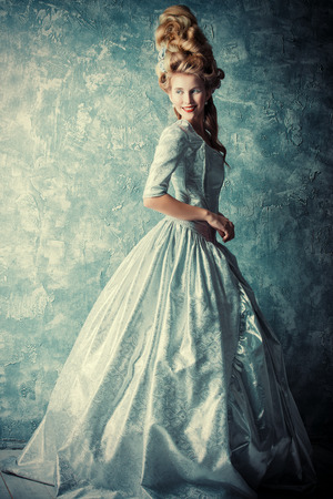 Fashion portrait of a beautiful woman in a luxurious medieval dress and high hairdo in vintage style. Baroque and Renaissance style. Historical dress, hairstyles history. Full length portrait. Imagens - 54824127