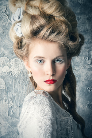 Fashion portrait of a beautiful woman in a luxurious medieval dress and high hairdo in vintage style. Baroque and Renaissance style. Historical dress, hairstyles history.