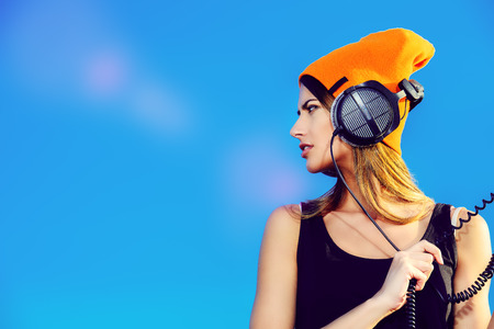 Modern young woman listening to music on headphones outdoor.