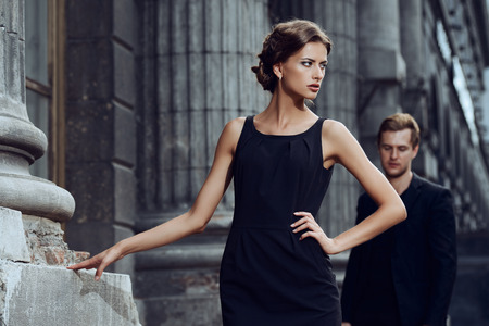 Fashion style photo of a beautiful couple over city background. Standard-Bild