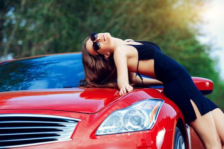 Aantrekkelijke jonge vrouw in de buurt van de rode sportwagen. Schoonheid, mode. Luxe leven.