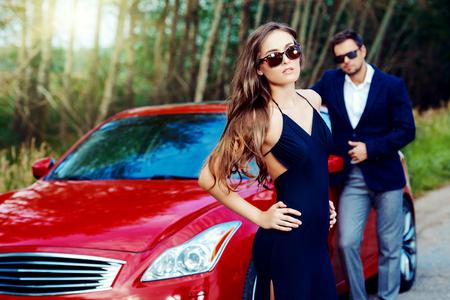 Pareja glamorosa cerca del coche. Belleza, la moda. Concepto del amor.