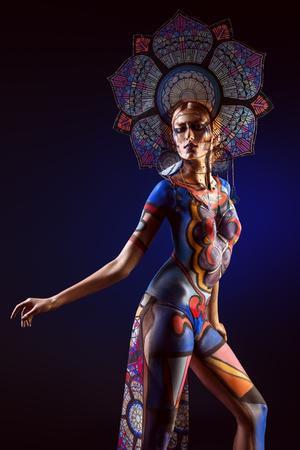 Projet d'art: portrait d'une femme avec des ornements colorés peints sur le corps et l'art coiffe. Body painting. Culture et art.