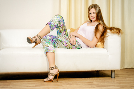 Modern young woman sitting on a sofa at home. Beauty, fashion. Stock Photo - 55507125