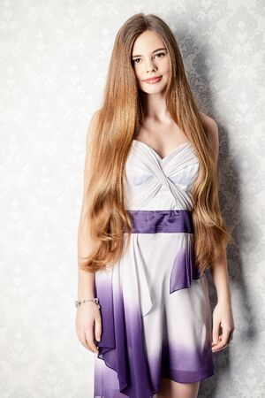 Beautiful girl with magnificent long hair posing in evening dress by vintage wall. Beauty, fashion. School prom.