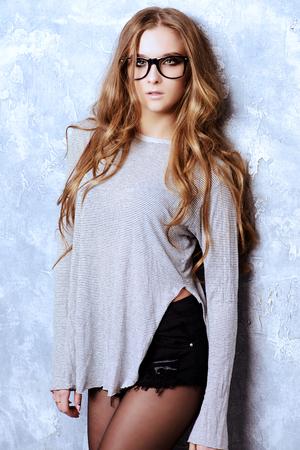 estilo de la óptica. Muchacha atractiva hermosa con largas gafas que llevaba el pelo ondulado. Captura de moda.
