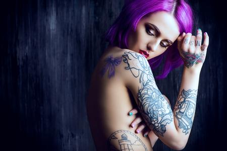 Schöne junge Frau mit stilvollen hochrot Haar und Tätowierung auf ihrem Körper über dunklen Grunge Hintergrund aufwirft. Haare färben. Kosmetik, Make-up. Tätowierung.