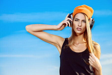 Modern young woman listening to music on headphones outdoor. Trendy teenager girt over blue sky background. Youth style. Banque d'images