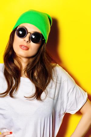 Trendy Mädchen mit Sonnenbrille und hellgrünen Hut, der durch eine gelbe Wand trägt. Helle Stil, Jugendmode.