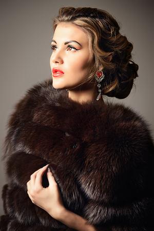 Close-up ritratto di una bella donna in cappotto di pelliccia di lusso. Di lusso, ricco stile di vita. Gioielleria. Moda girato.