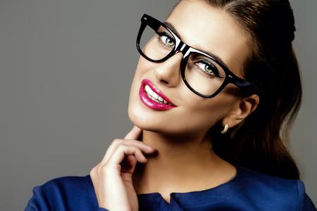 Optics style. Portrait of a beautiful young woman wearing elegant glasses. Beauty, fashion. Cosmetics, make-up.