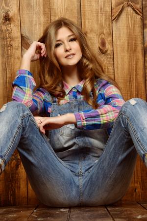 Muy niña en ropa de jeans ocasional que se sienta por una pared de madera. estilo de la juventud.